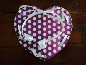 Continue weaving the ribbon through the holes on each side, and then tie a bow once you reach the middle hole.