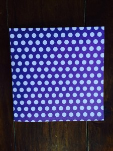 Start by folding a square sheet of craft paper in half, and then again, to create a small square.